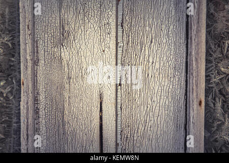 Vintage winter background with old wooden bleached surface with frost pattern frame on frozen window as Christmas - Stock Photo