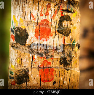 Colourful childrens handprints on a palm tree trunk - Stock Photo