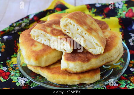 Homemade apple pies on a glass plate on a multicolored cloth. - Stock Photo