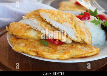 Turkey schnitzel on a plate with rice, lettuce, chili pepper and cherry tomatoes on a wooden board on an abstract - Stock Photo