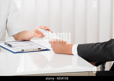Close-up Of Female Doctor Hand Giving Prescription To Businessman - Stock Photo