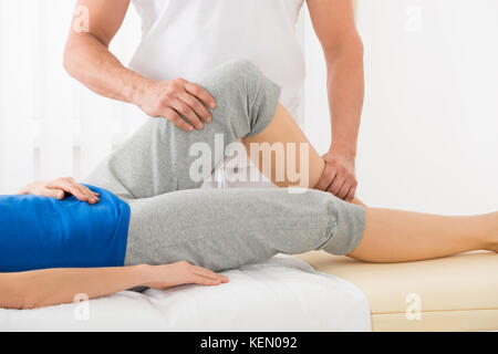 Close-up Of Therapist Hand Doing Knee Massage In Spa Saloon - Stock Photo