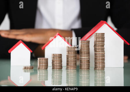 Close-up Of Businesswoman With Different Size Of House Model And Stacked Coins On Desk