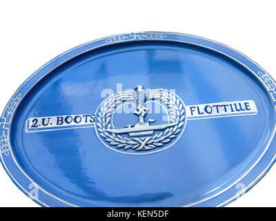 Blue ceramic plate to commemorate Nazi U Boats Flotilla with swastika emblem produced during WW2 near Nazi U Boat - Stock Photo