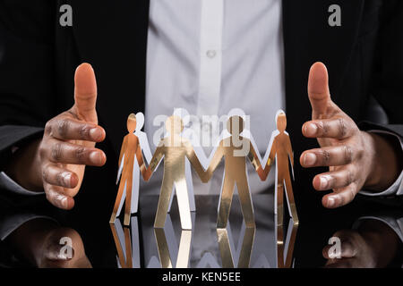 Close-up Of Businessperson Protecting Cut-out Figures On Desk - Stock Photo