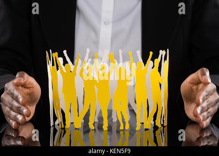 Close-up Of Businessperson Hand Protecting Cheering Paper Cutout People On Desk - Stock Photo