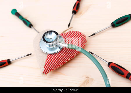 Fabric red heart, stethoscope and srewdrivers around on wooden table - health condition and healthcare concept - Stock Photo