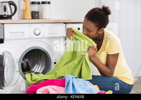 Young African Woman Smelling Clothes After Washing At Home - Stock Photo