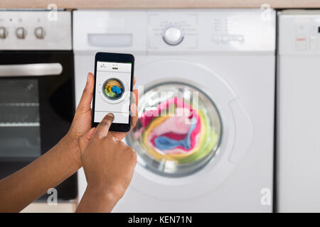 Close-up Of Woman's Hand Operating Washing Machine With Mobile Phone In Kitchen - Stock Photo