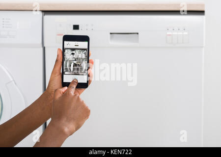Close-up Of Woman's Hand Operating Dishwasher With Mobile Phone In Kitchen - Stock Photo
