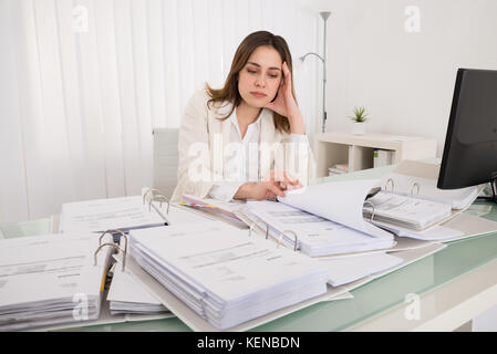 ... Tired Young Accountant Working With Papers In Office   Stock Photo