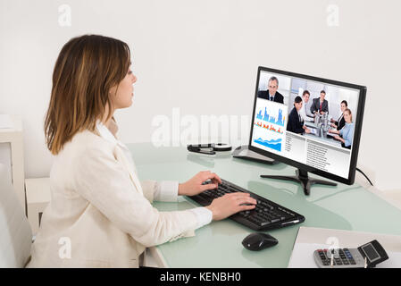 Young Businesswoman Video Conferencing On Computer In Office - Stock Photo