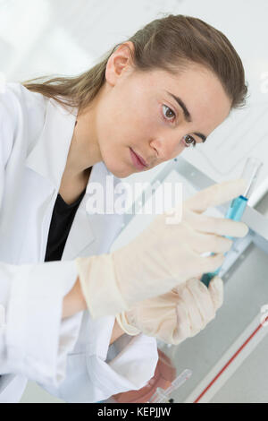 young female researcher loads samples for pcr testing - Stock Photo