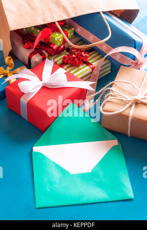 Cheerful image with a green envelope with blank paper surrounded by multicolored presents, that came out of an overturned - Stock Photo