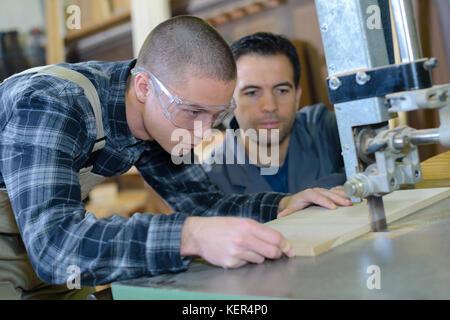 apprentice with cut machine - Stock Photo