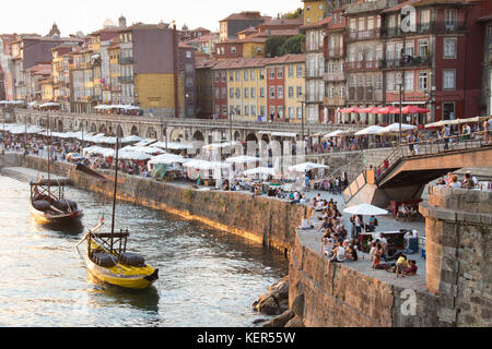 Tourists and locals enjoying the river, drinks and the sunset, Porto, Portugal - Stock Photo