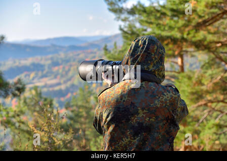 Wildlife, nature man photographer in camouflage outfit shooting, taking pictures - Stock Photo