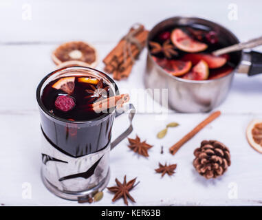 mulled wine in a glass with an iron cup holder on a white wooden background, top view - Stock Photo