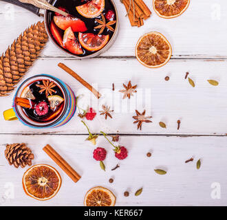 mulled wine in a mug and ingredients for making a drink on a white wooden background, top view - Stock Photo