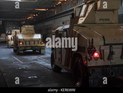 Humvee trucks drive through the well deck of the amphibious dock landing ship USS Gunston Hall (LSD) - Stock Photo