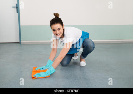 Young Happy Female Janitor Cleaning Floor With Duster - Stock Photo