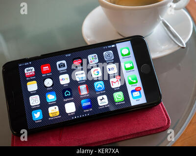 iPhone 7 Plus on modern French cafe table in folio case, landscape orientation with UK based screen apps on display - Stock Photo