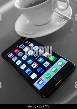 iPhone 7 Plus on modern French cafe table vertical orientation with screen apps on display French roaming SFR in - Stock Photo
