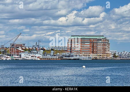 The USS Cassin Young and the Flagship Wharf with a blue sky and white fluffy clouds. - Stock Photo