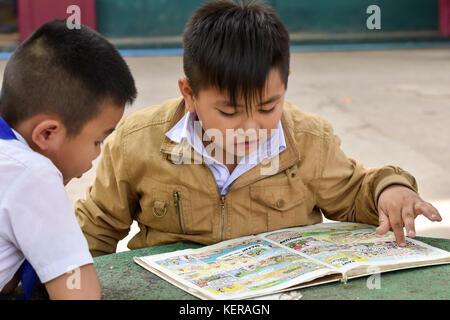 Schoolchildren reading Vientiane Laosscho - Stock Photo