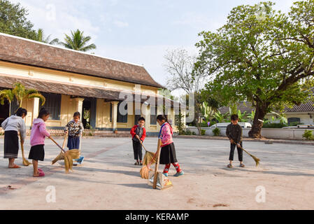 Schoolchildren cleaning schoolyard in the morning Luang Prabang Laos - Stock Photo