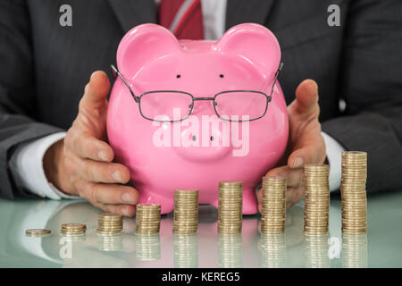 Close-up Of Businessman Hand Covering Piggy Bank With Stacked Coins At Desk - Stock Photo