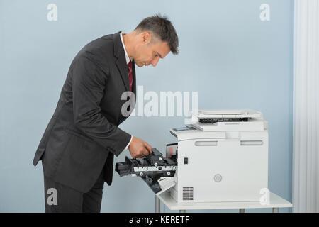 Mature Businessman Fixing Cartridge In Printer Machine At Office - Stock Photo