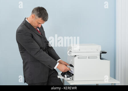 Irritated Mature Businessman Removing Paper Stuck In Printer At Office - Stock Photo