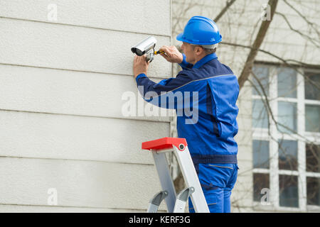 Mature Male Technician Standing On Stepladder Fitting CCTV Camera On Wall - Stock Photo
