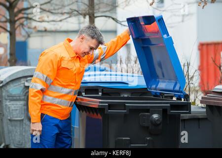Working Man Looking In Dustbin On Street - Stock Photo