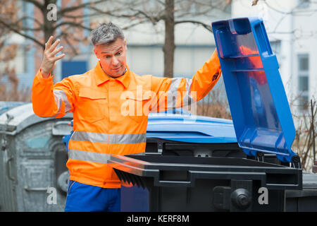Unhappy Male Street Cleaner Looking In Dustbin - Stock Photo