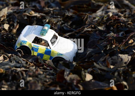 Plastic discarded toy- police car cops it on the soft shoulder of seaweed on the  high tide line - Stock Photo