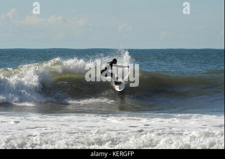 Surfer carves a turn -going for it on a fast Gower wave - Stock Photo