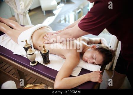 Young Woman Enjoying Massage in SPA - Stock Photo