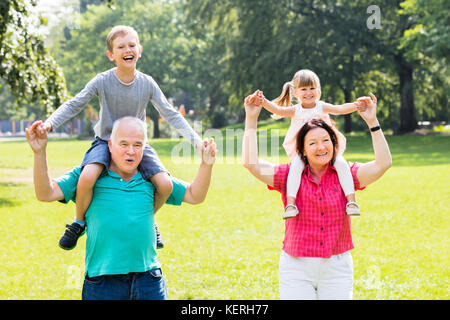 Happy Family Having Fun With Kids Doing Piggyback Ride In Park - Stock Photo