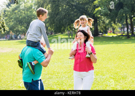 Happy Old Grandparents Giving Piggyback Ride To Their Grandchildren In Park - Stock Photo