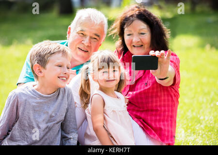 Happy Family Taking Selfie With Phone In Park - Stock Photo