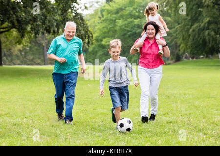 Happy Family Playing Soccer Game Together Running For Ball - Stock Photo