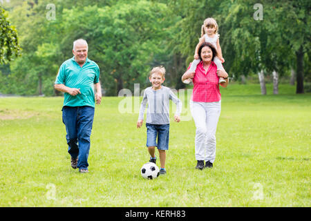 Happy Family Playing Soccer Game With Grandchildren Together In Park. Running For Ball - Stock Photo