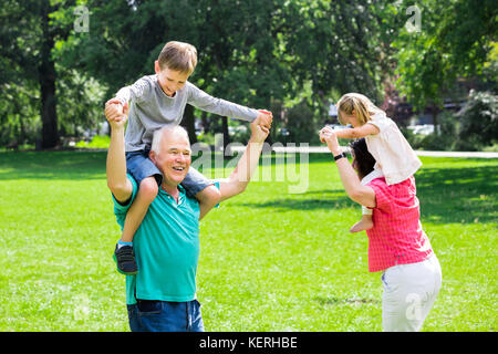 Happy Family Having Fun Doing Piggyback Ride With Kids In Park - Stock Photo