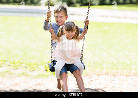 Two Happy Children Enjoying On Swing In The Park - Stock Photo