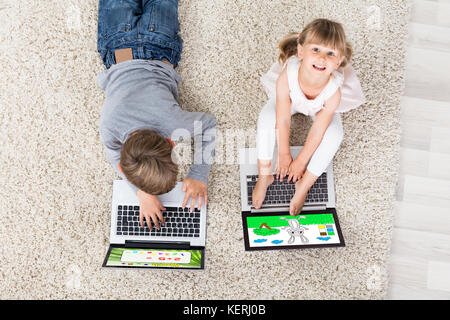 Two Kids With Laptop Computers On Carpet At Home - Stock Photo
