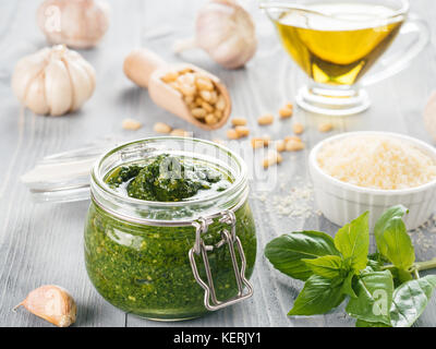 Homemade pesto sauce and ingredients on gray wooden background. Close up wiev of basil pesto in glass jar with ingredients. - Stock Photo