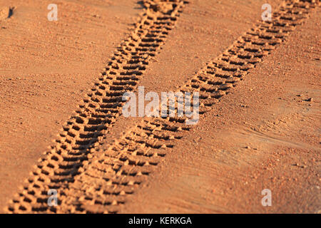 Traces of tire treads on orange sand, diverging in different directions. - Stock Photo