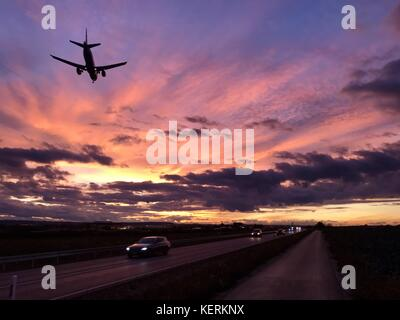 A plane is approaching Stuttgart AIrport during a dramatic sunset - Stock Photo